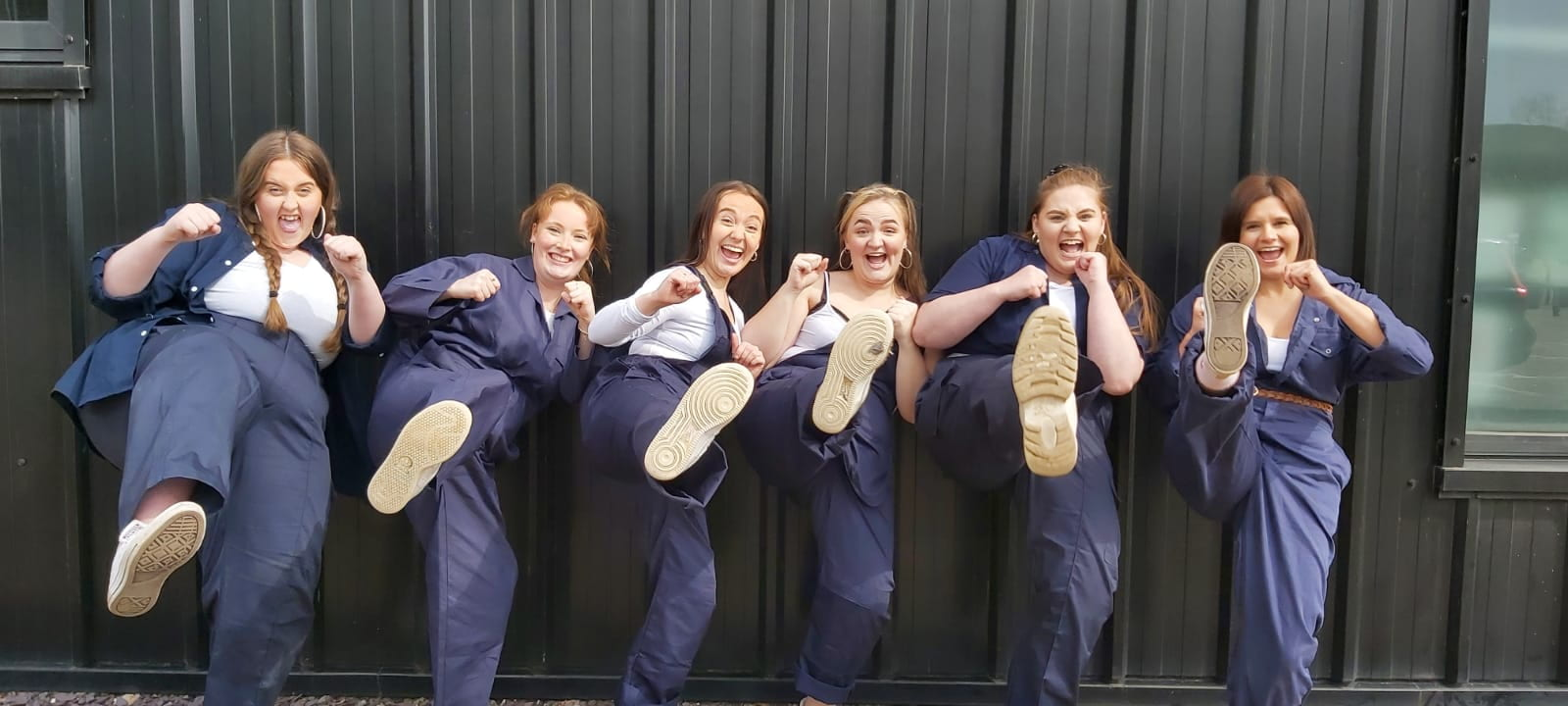 Image contains six women kicking their feet up to the camera. All dressed in men's workwear.