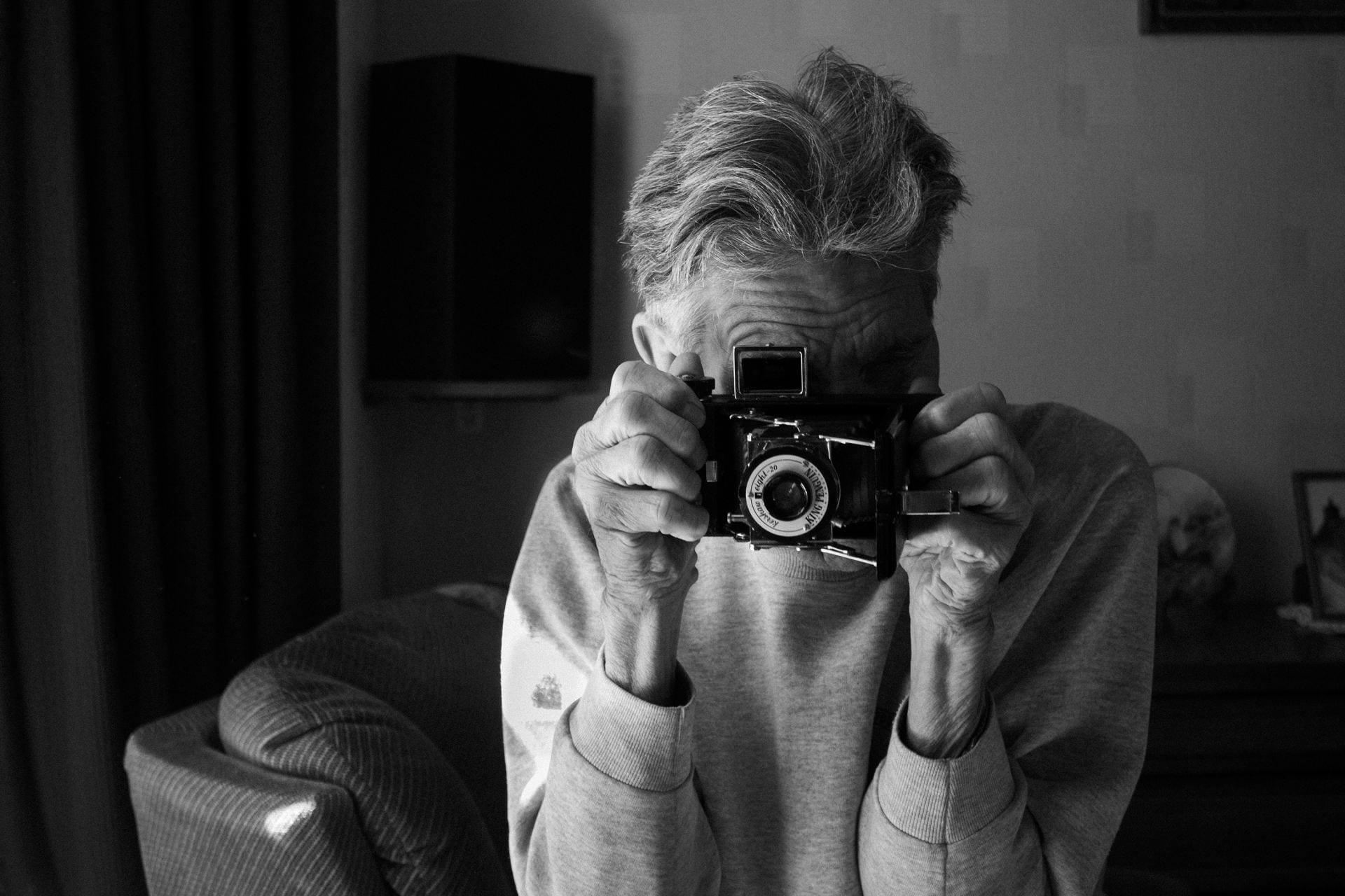 Black and white photograph of man holding a camera.