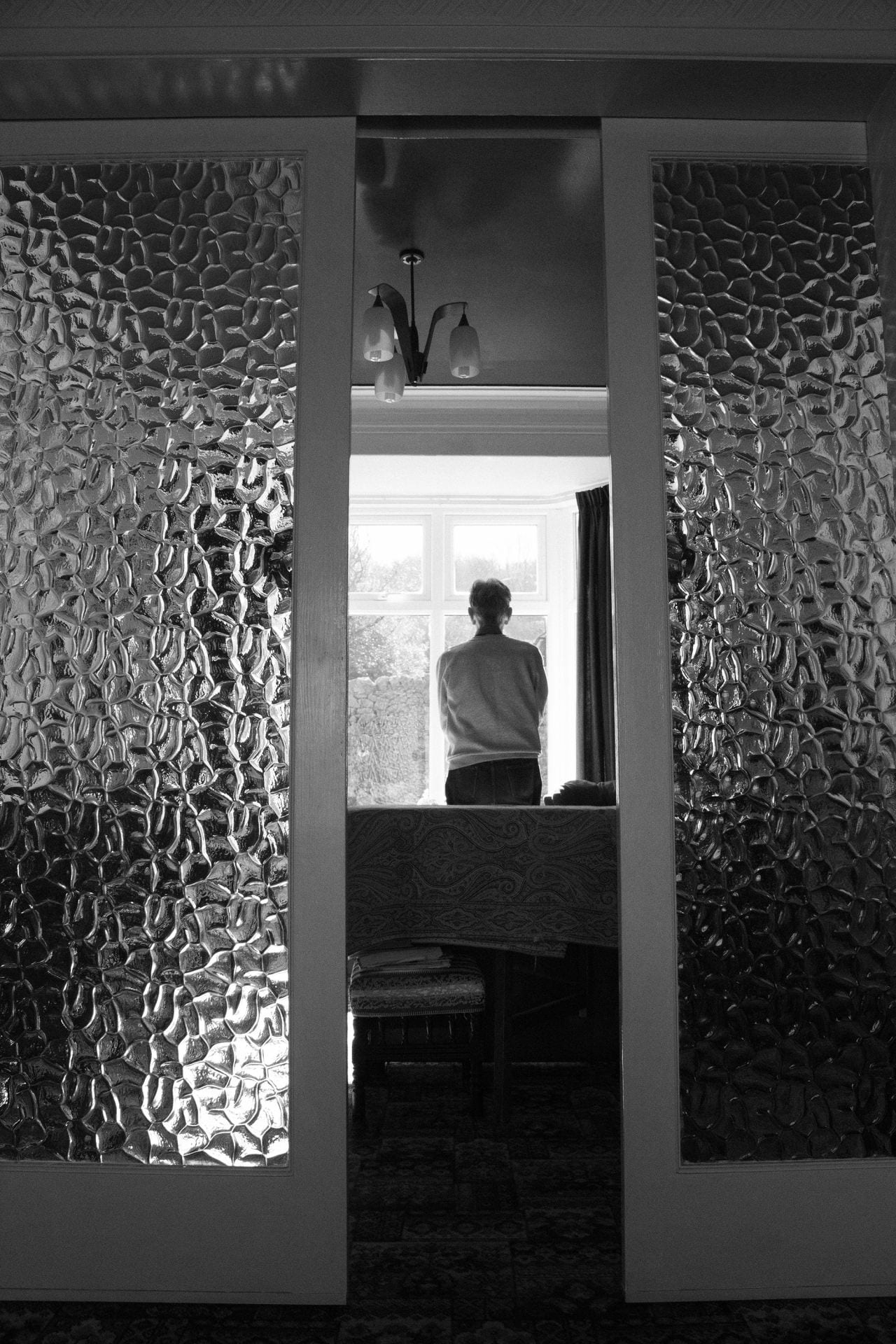 Black and white photograph of man standing by a window.