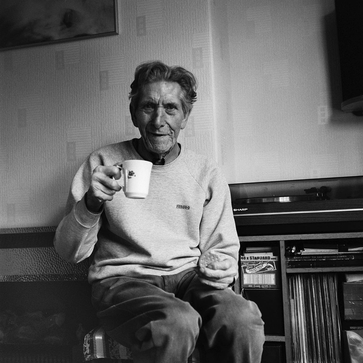 Black and white photograph of man holding a mug.