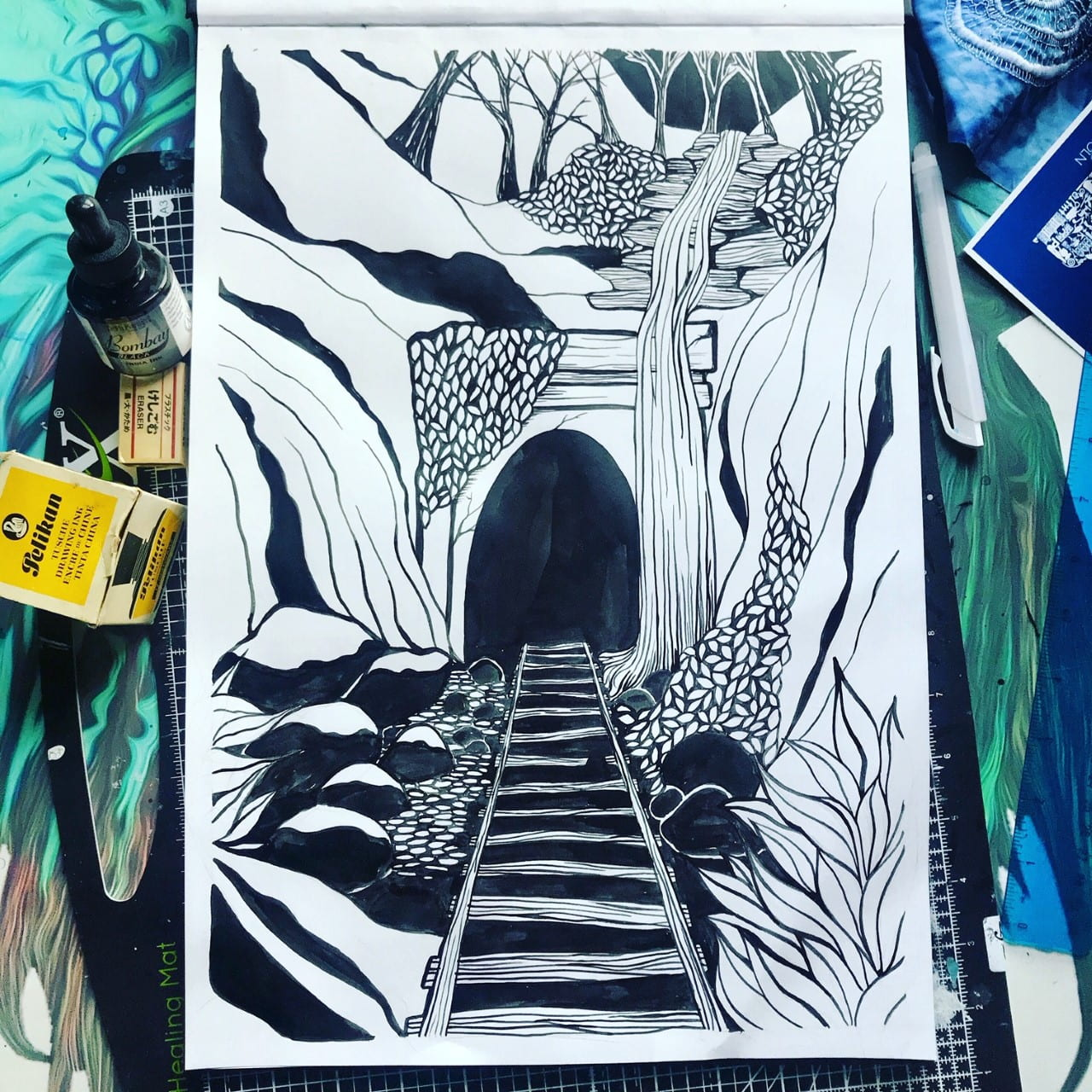 Photograph of a Lino Print of an Abandoned Train Tunnel surrounded by art equipment.