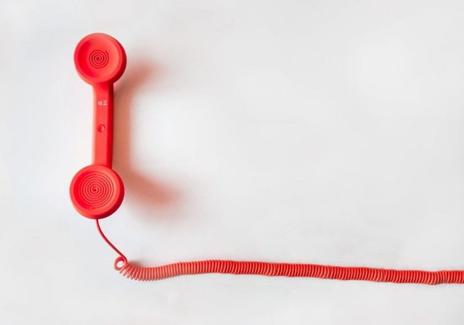 Student Services - A red cord phone on a white backdrop.