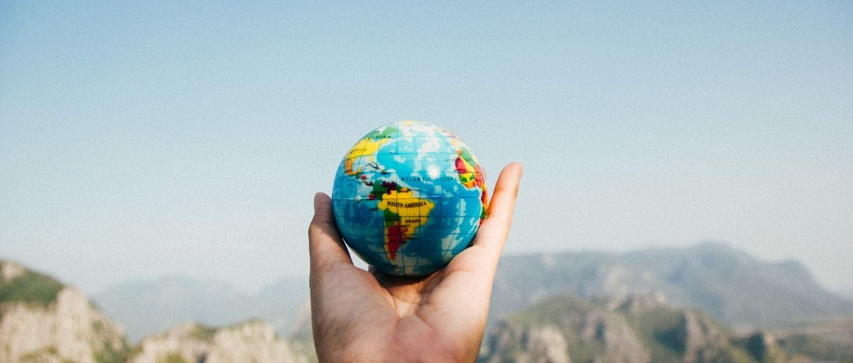 Student Services - A hand holding a miniature globe in front of a landscape.