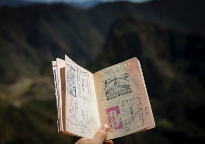 Student Services - A passport with lots of stamps held in front of a landscape.
