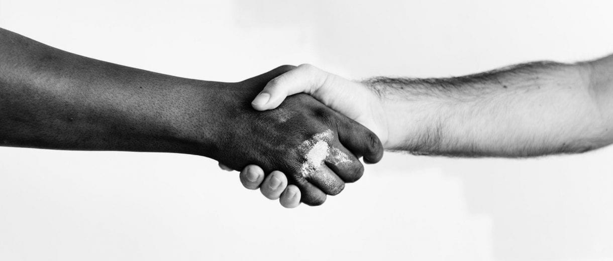 Student Services - Two people shaking hands in front of a white background.