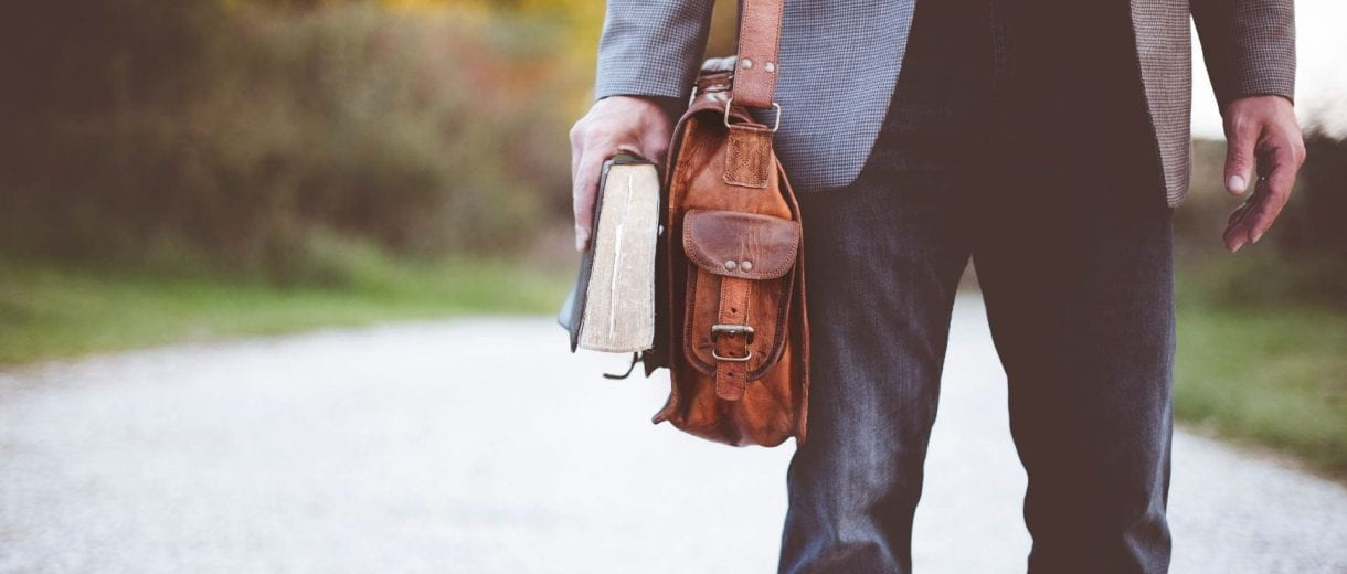 Student Services - A waist down shot of a main wearing a suit jacket holding a book and a satchel.