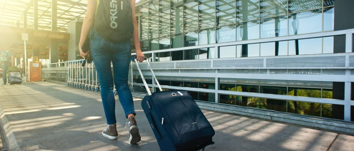 Student Services - Woman pulling suitcase through airport.
