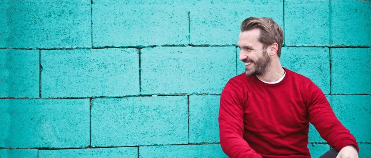 Student Services - Smiling man in red jumper crouched leaning against teal coloured wall.