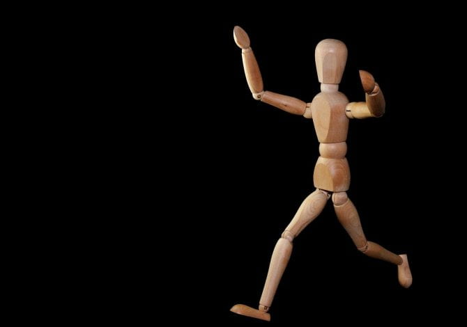 Student Services - Wooden miniature mannequin posed running.