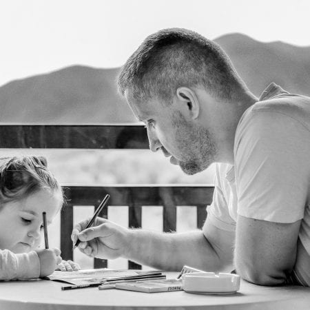 This picture is in blackboard and white. it shows a girl and a man writing on a document. There is a view of the sea and mountains in the background.