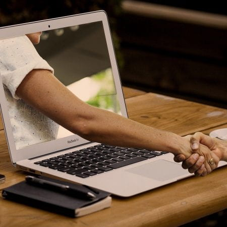 A picture of a laptop with a hand coming through the screen. This hand is connected to someone elses hand who is looking at the laptop. They are shaking each others hands.