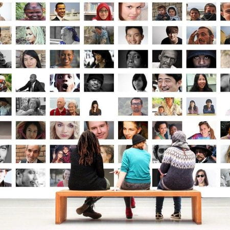 Three people sitting on a brown bench. They are looking at a wall with multiple squared pictures of different people.