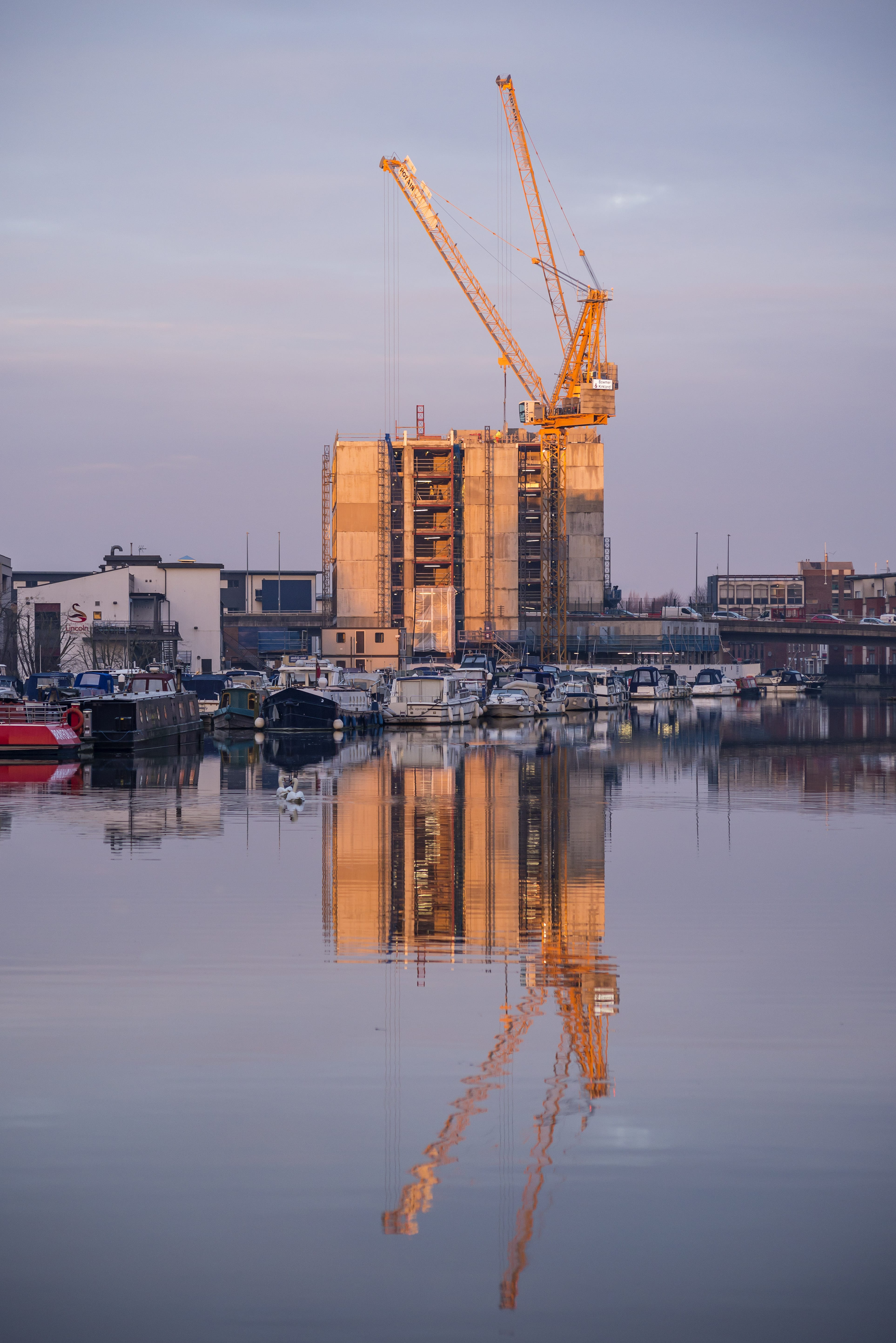 Image of an accommodation block being built by the water, a crane towers above it.