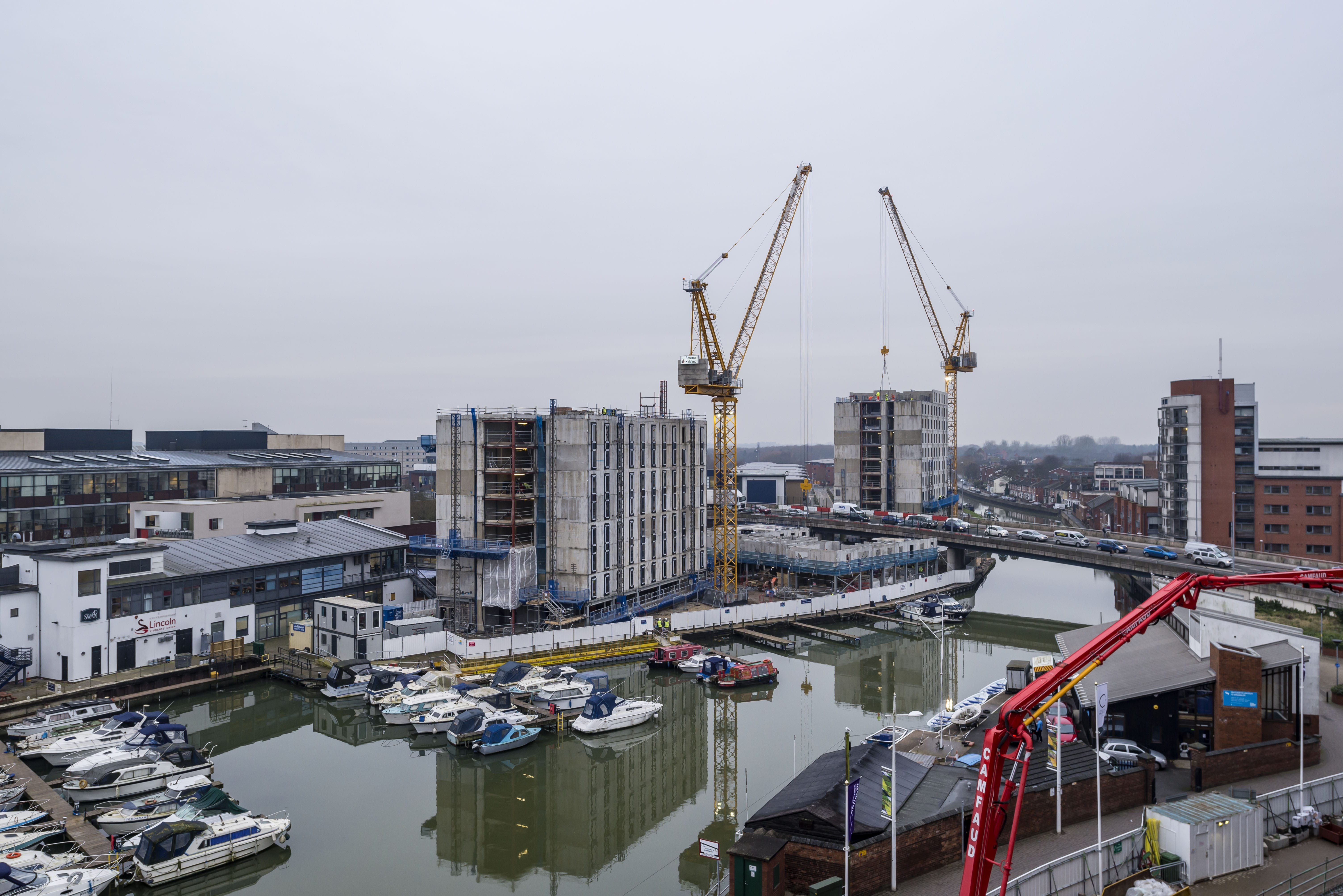 Image of the an accommodation block being built, two cranes work across a flyover