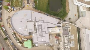 Aerial image of a large building and surrounding cars.