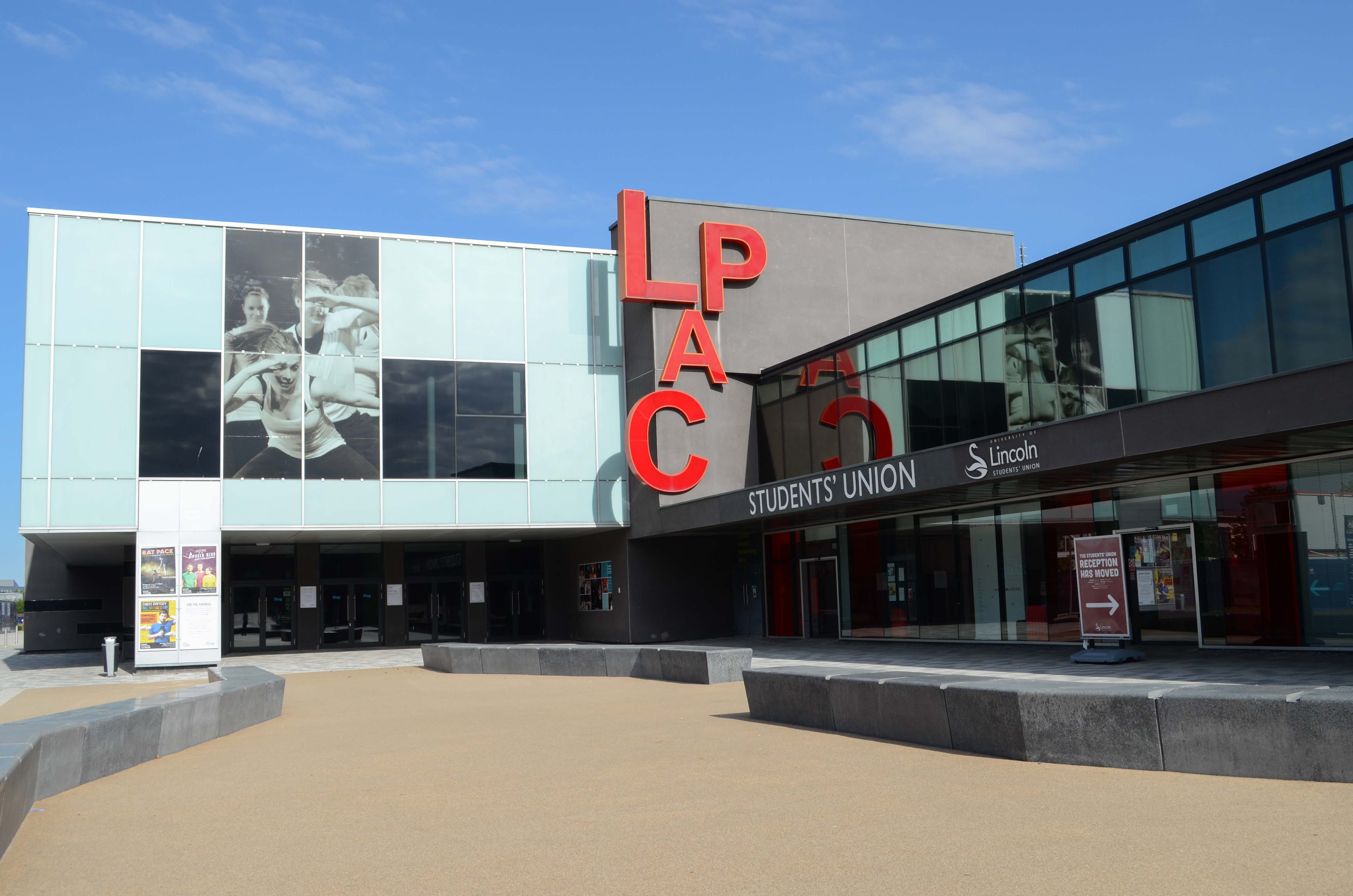 """Image of a theatre, a large light blue and grey building with """"LPAC"""" signage in red"""