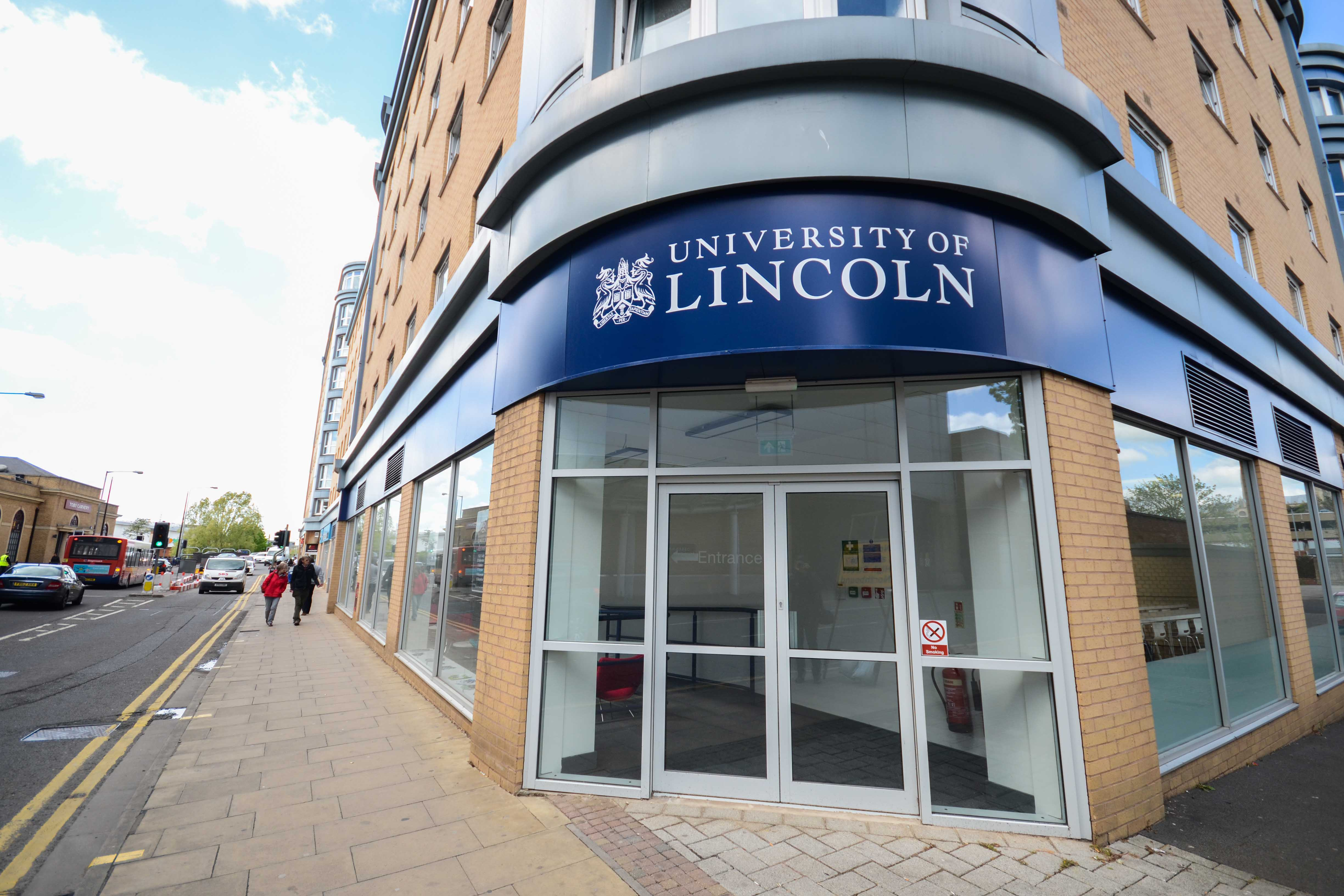 Image of a rounded front entrance to a ground floor section of a building. A University of Lincoln banner is above the doorway in blue.