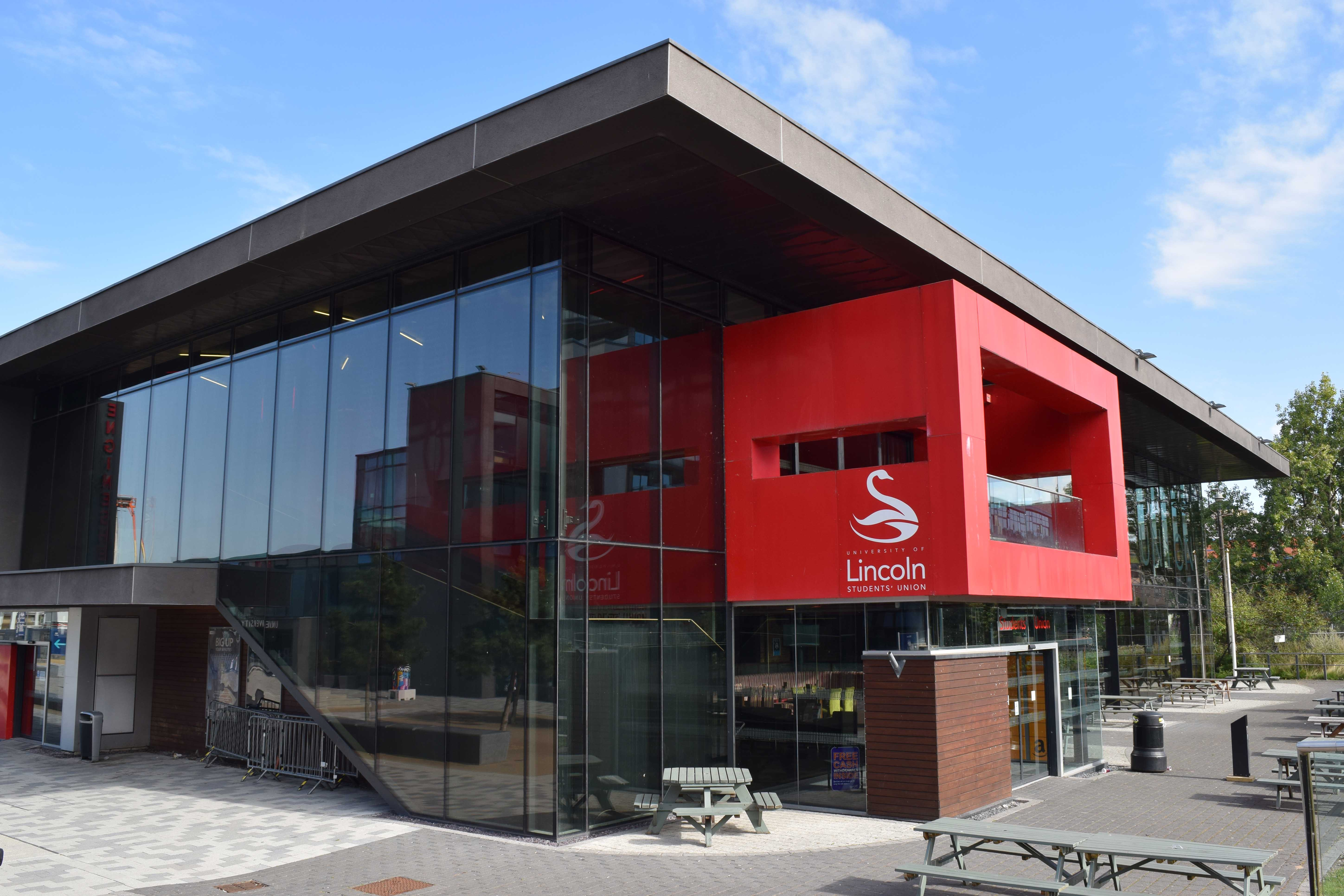 Image of a building with a glass wall and red platform