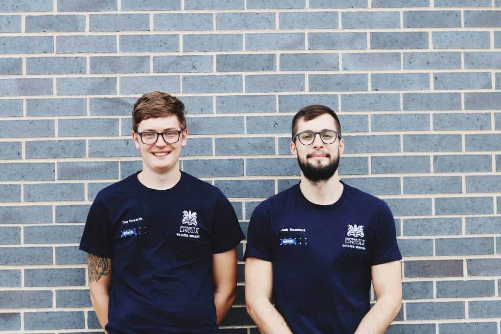 Pictured: Tom and Josh in their Engineering uniform, dark blue shirts. There is a grey brick wall behind them.