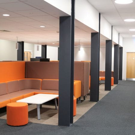 Image of a social learning space, including orange sofas and white tables. The furniture has inbuilt power.