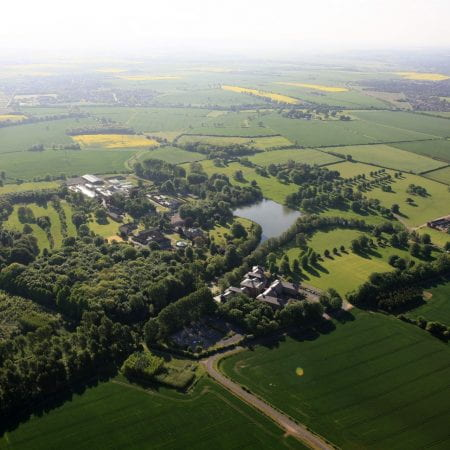 Aerial image of a green university campus with fields and woodlands surrounding it