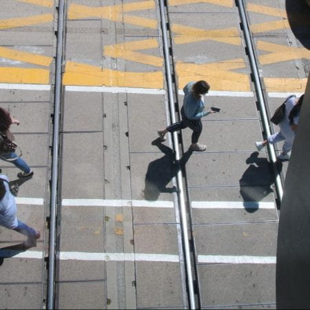 Image of the railway lines with people walking across the crossing