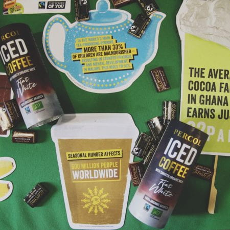Image of some iced coffee cartons laid on a table with leaflets and small packets of chocolate