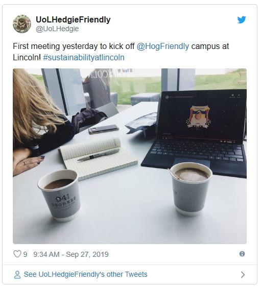 Image of a screenshot Tweet on Twitter, in the image there is a laptop, two cups and a person writing in a notebook