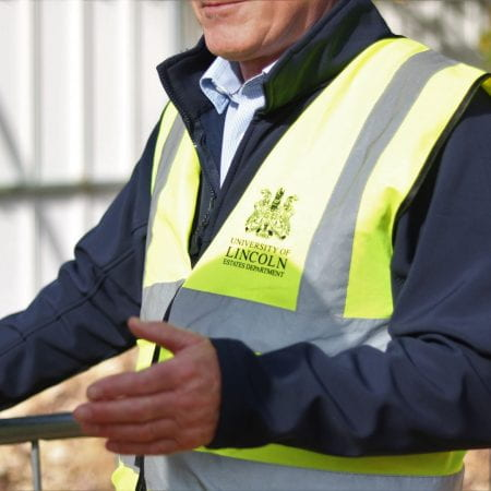 Image of a person gesturing at something. They are wearing a high visibility reflective vest with the university logo on it