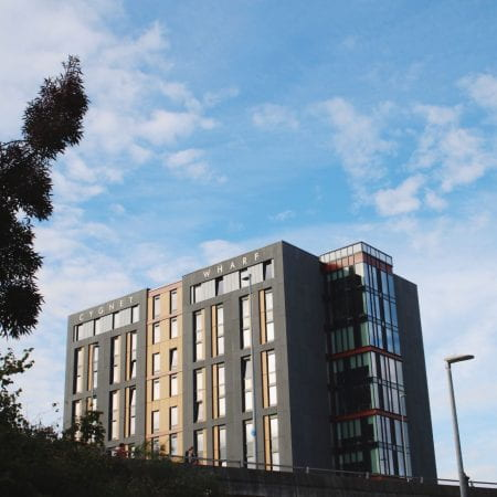 Image of an accommodation tower block with a blue cloudy sky surrounding