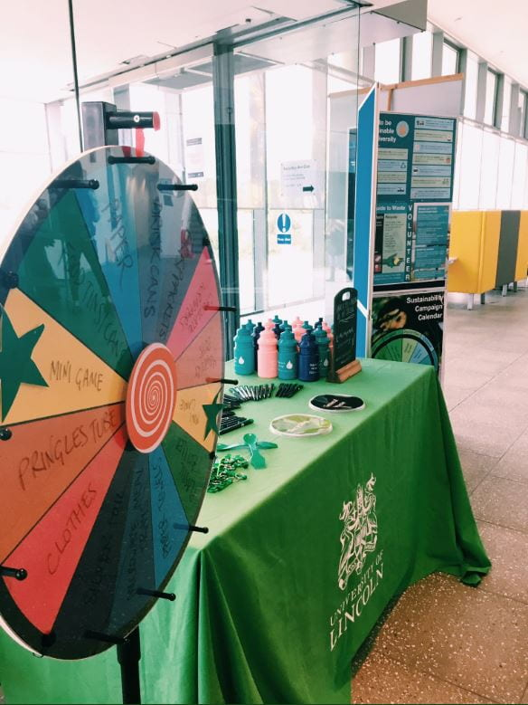 Image of an exhibition stand with a colourful wheel with recycling based topics on it.