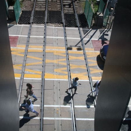Image of some people walking across a railway crossing from above