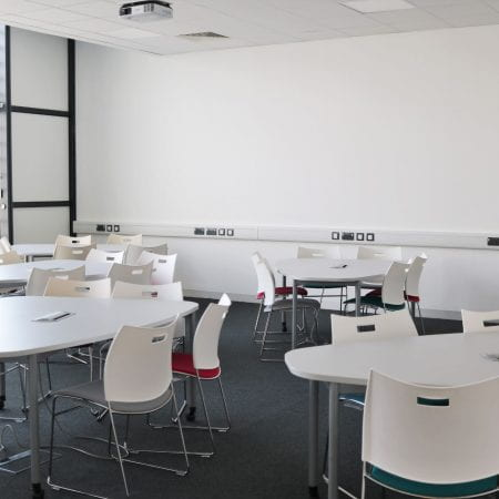 Image of a seminar room with round tables and chairs