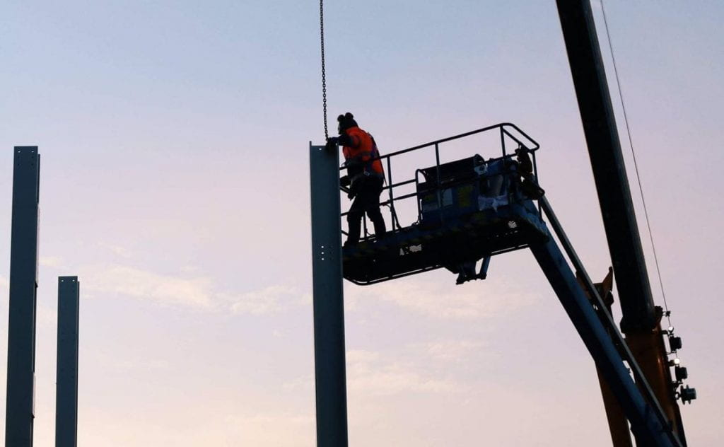 Image of a worker on a crane near steel frame works