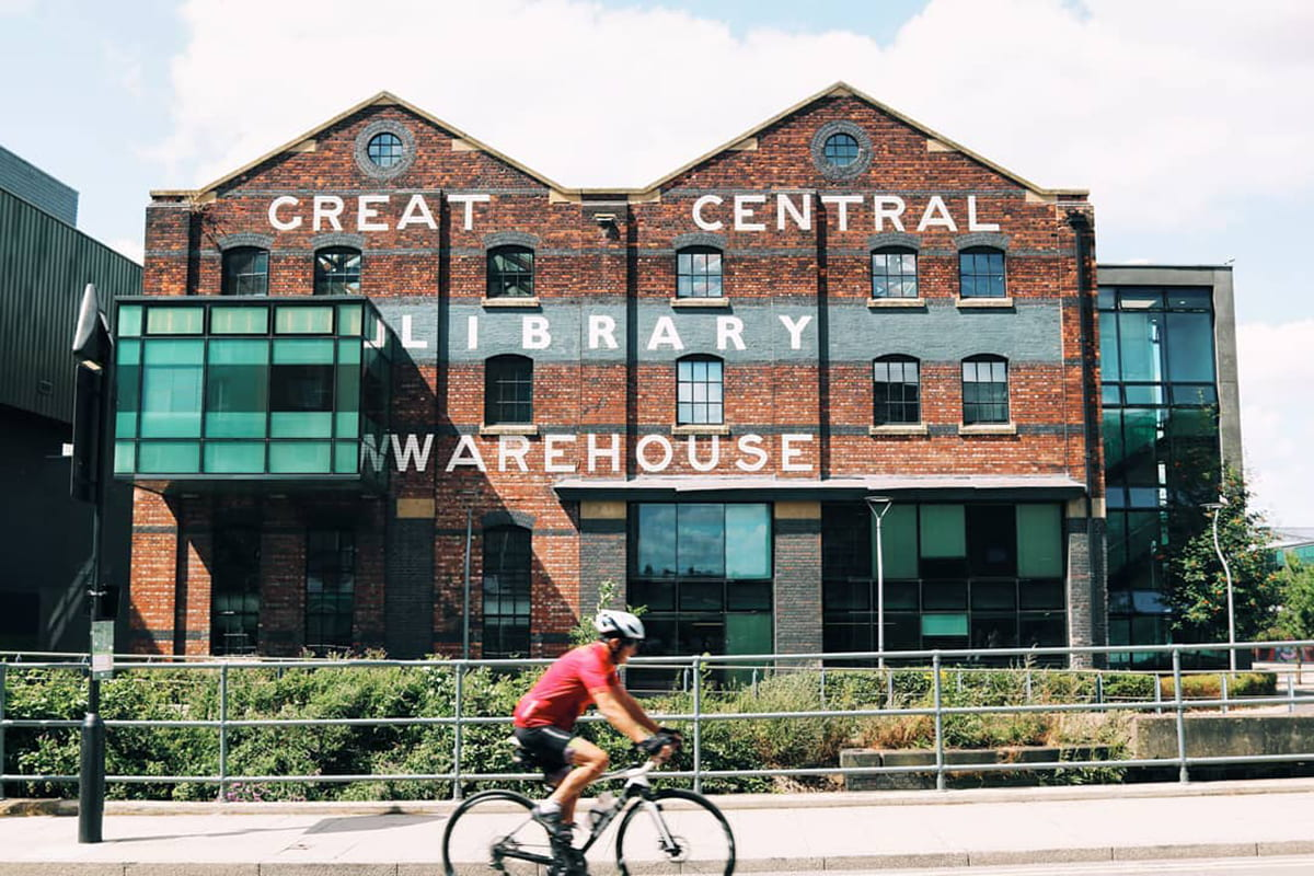 Image of a building with a cyclist in front of it