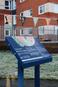 Image of a blue lectern style sign in a green frosty area. There are planters in the background.