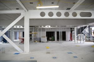 Image of a large room in construction. The walls and ceiling are bare