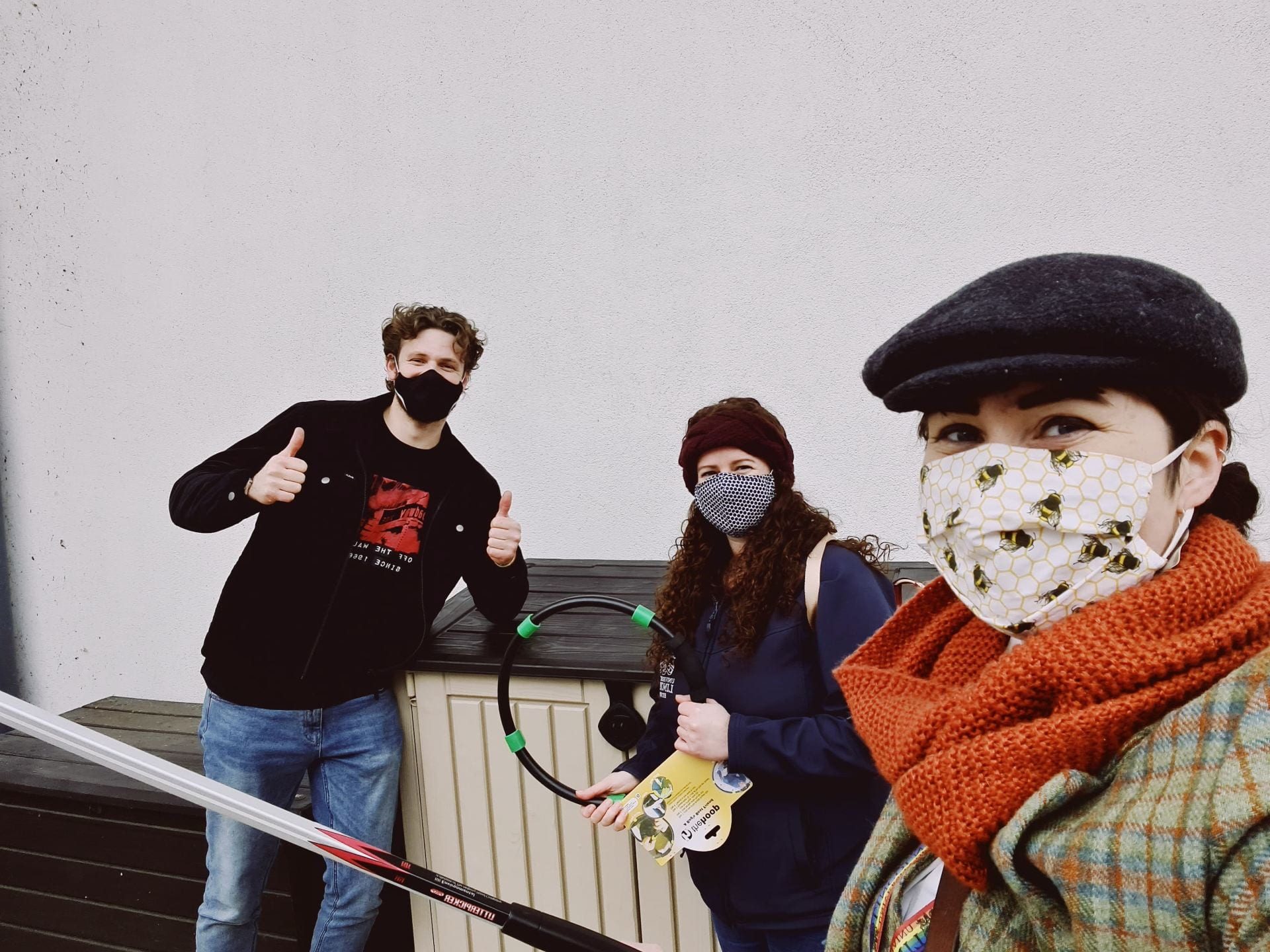 Three people hold litter picking equipment and look happy under their masks. They are socially distanced.