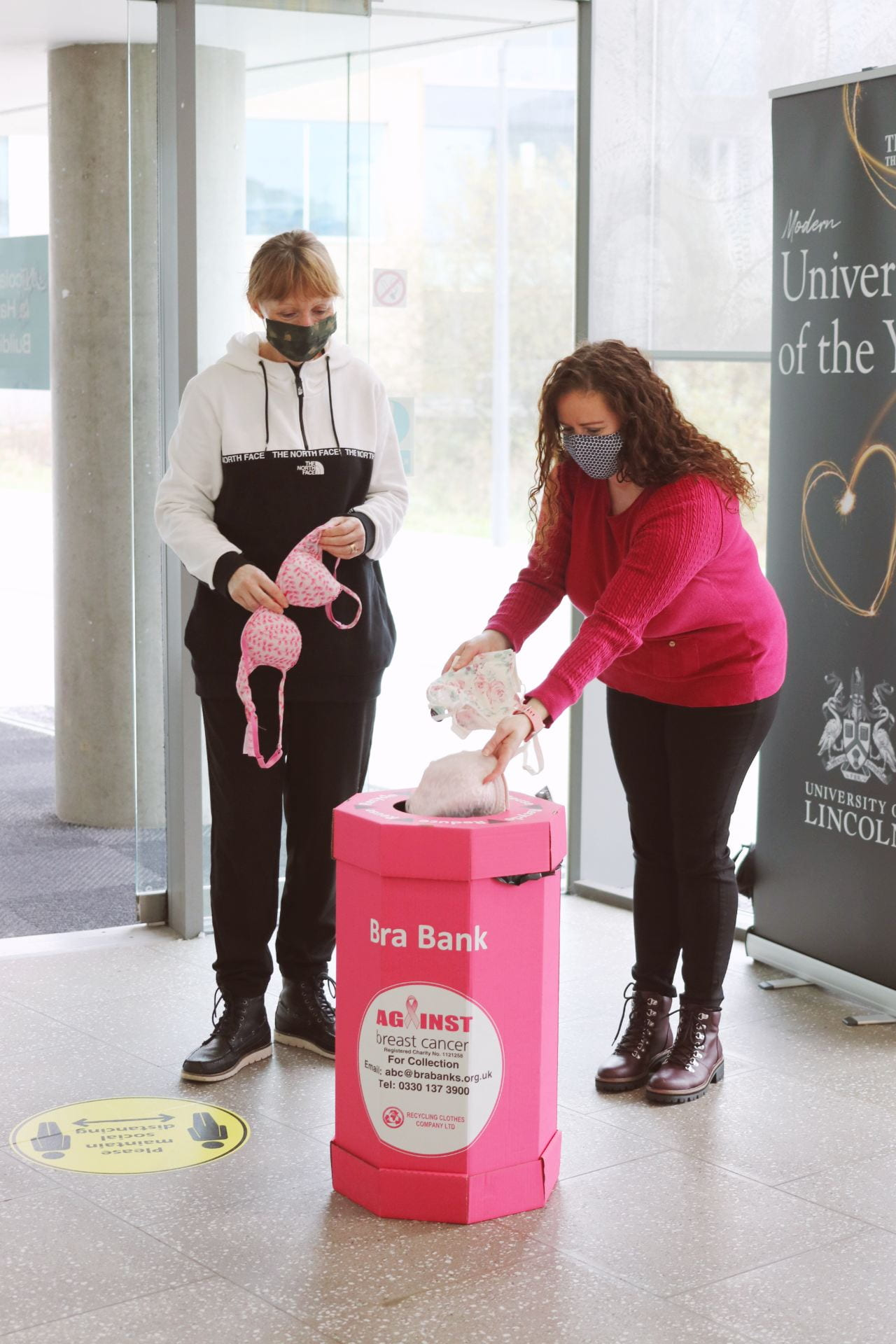 Image of two people putting bras into a pink recycling bin
