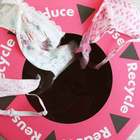 Image of a pink recycling bin with bras on top of it. The word recycle is printed on the lid.