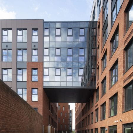 """Image of tall building blocks with a glass building """"bridged"""" between them"""
