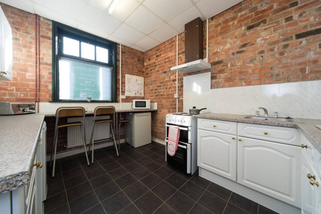 College Mews Example Kitchen showing breakfast bar and kitchen cupboards.