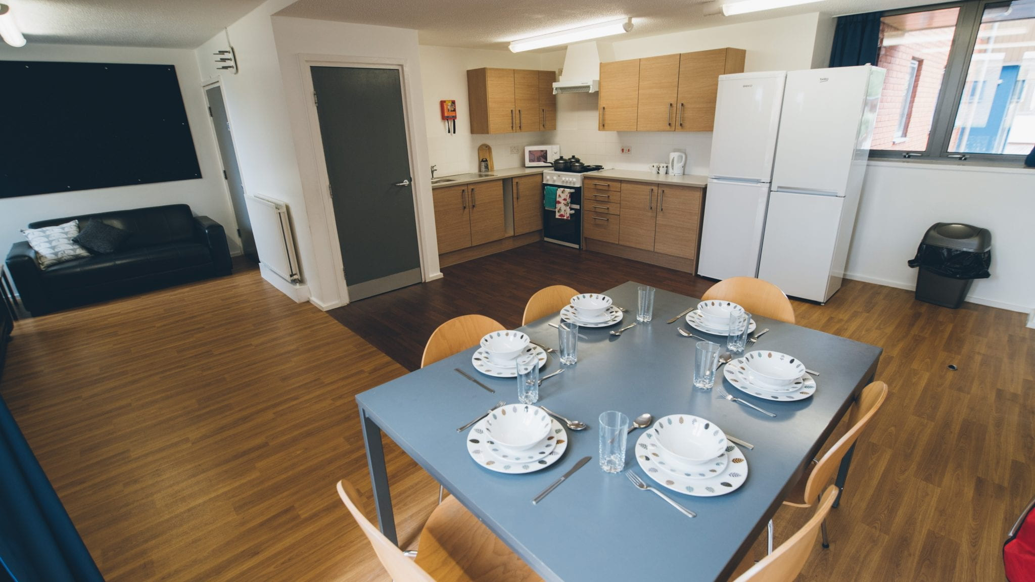 An example Lincoln Courts kitchen showing dining table & chairs, kitchen worktops and cupboards. Showing the room dressed with crockery cutlery and pots and pans (these are not provided & are shown for decorative purposes only).