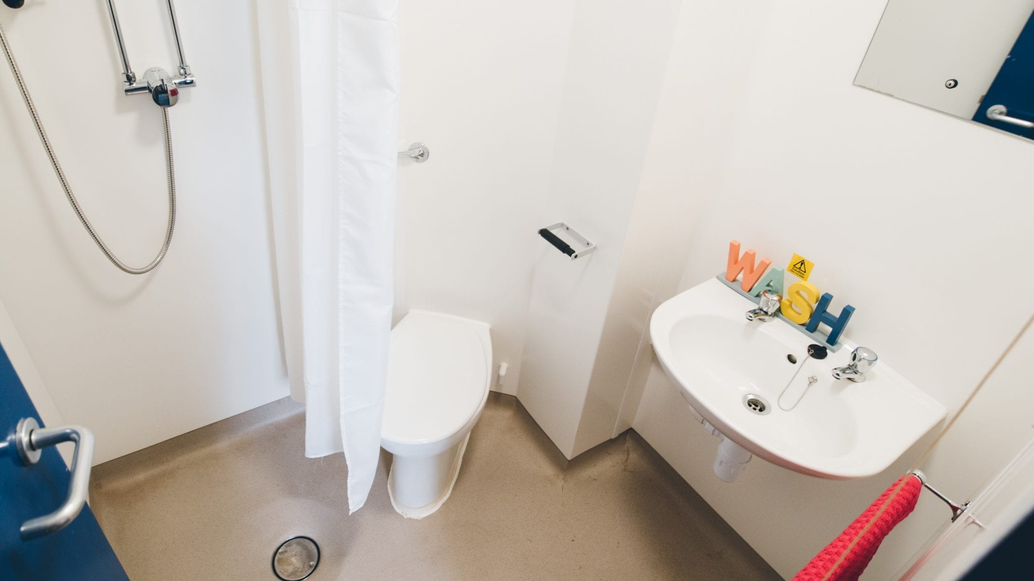 Lincoln Courts en-suite wet room style bathroom including a shower, shower curtain and basin.