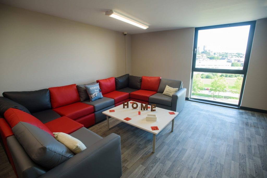 The Gateway communal lounge showing sofas seating, coffee table and large window,