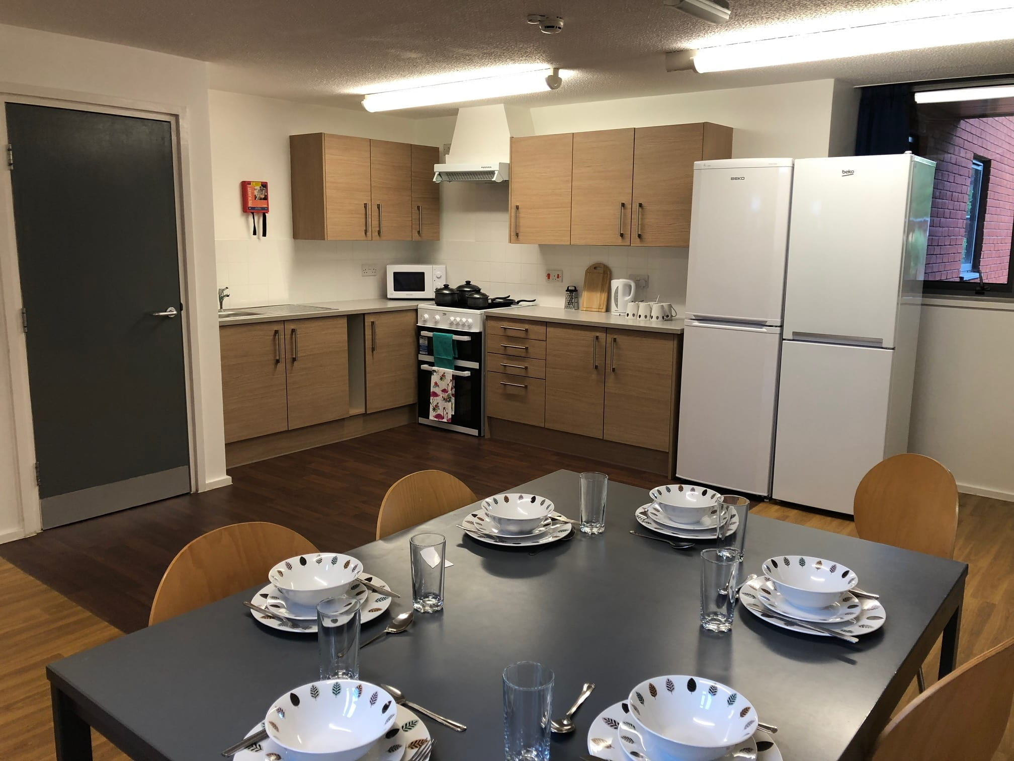 An example Lincoln Courts kitchen showing dining table & chairs, kitchen worktops and cupboards. showing the room dressed with crockery cuttlery and pots and pans (these are not provided & are shown for decorative purposes only).
