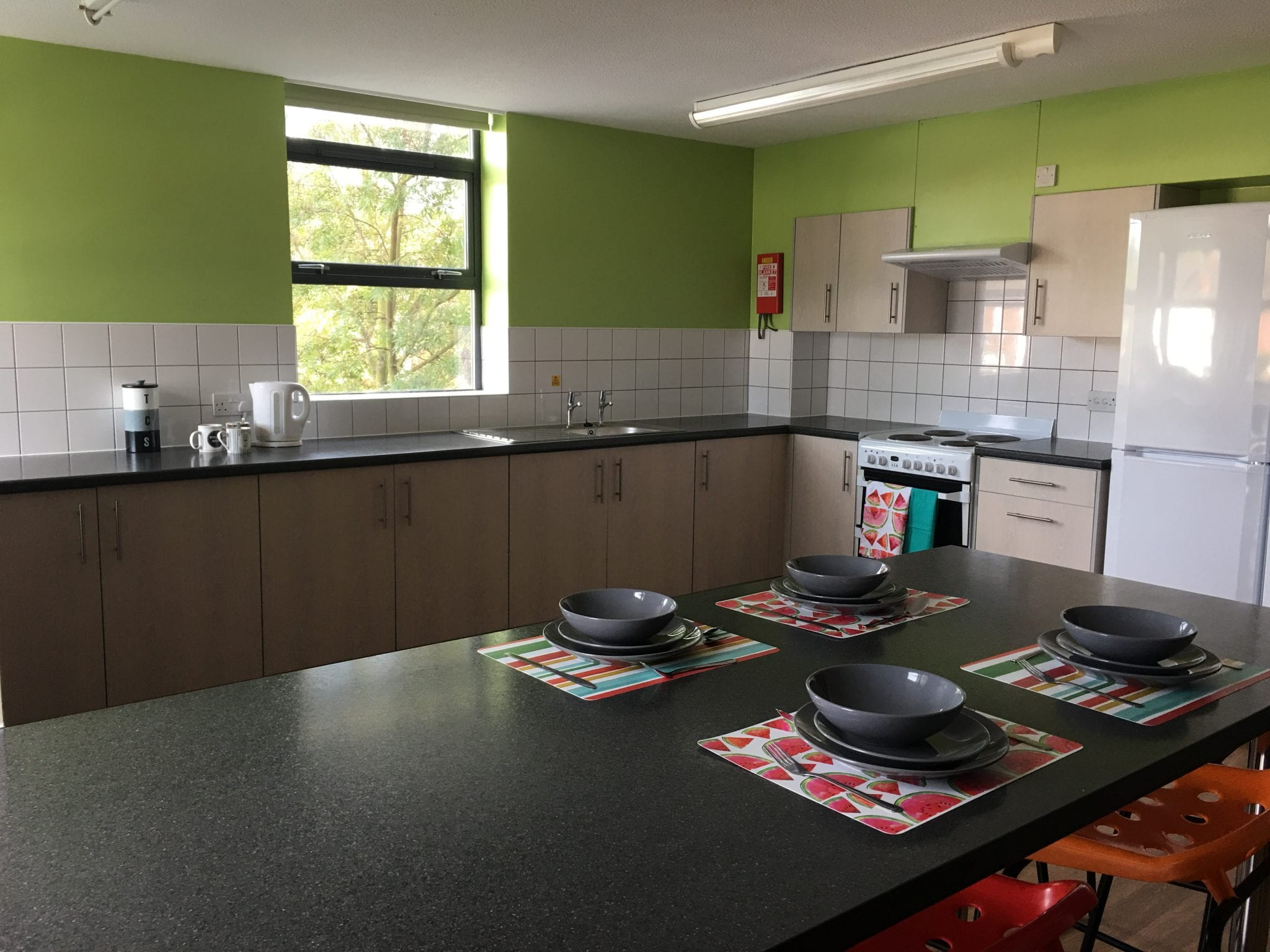 An example Lincoln Courts kitchen showing breakfast bar, kitchen worktops and cupboards.