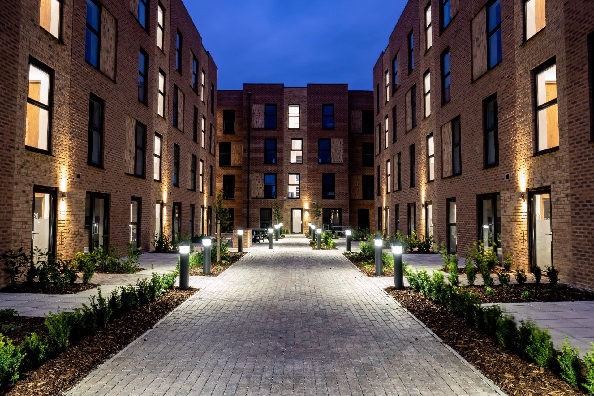 Exterior shot of Valentine Court showing BBQ pit and wooden benches.