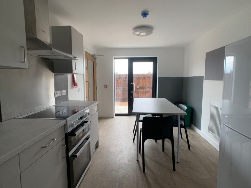 Valentine Court kitchen showing fridge-freezers, oven, kitchen cupboards, noticeboard, table and chairs.