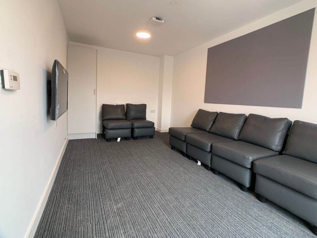 Valentine Court lounge showing communal cleaning cupboard, tv, sofas and noticeboards.